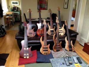 Edo's Bass Lair (l-r on sofa: Erizias 7 String Fretless, Alex Watson 7-String Fretless, Muckleroy 7-String Fretless, Jerzy Drozd 7-String Barcelona; l-r on floor: Utrera Prestige 7-string bass (first one ever built), Conklin Custom Sidewinder 7-string with Zebrawood, Conklin Custom Sidewinder bass Walnut Top with Midi, Bee Bass 7-string Modern Retro with Spalted Maple top).